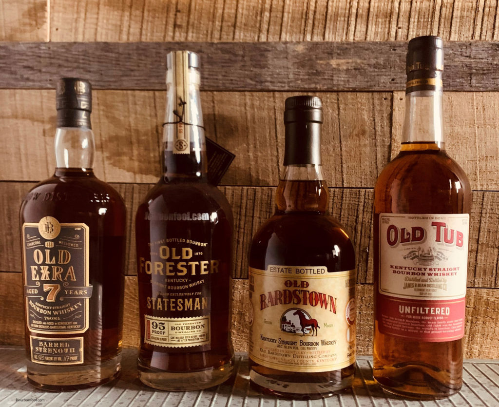 Four bottles of Old Whiskey. Old Ezra 7, Old Forester Statesman, Old Bardstown, and Old Tub.